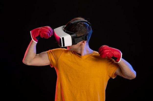 Jeune homme jouant à la réalité virtuelle dans des gants mma sur une surface sombre