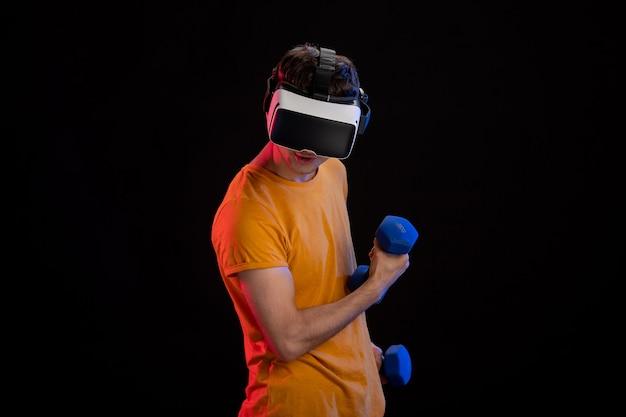Jeune Homme Jouant à La Réalité Virtuelle Avec Des Haltères Sur Une Surface Sombre Photo Premium