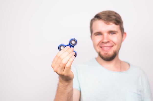 Jeune homme jouant avec un spinner fidget, se concentrer sur le spinner.