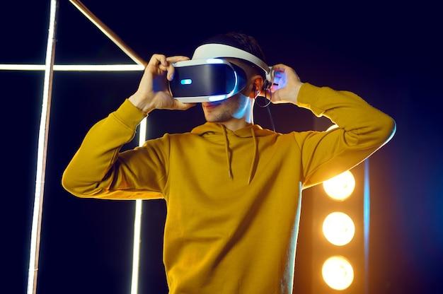 Jeune homme joue au jeu en utilisant un casque de réalité virtuelle et une manette de jeu en cube lumineux. intérieur du club de jeu sombre, technologie vr avec vision 3d