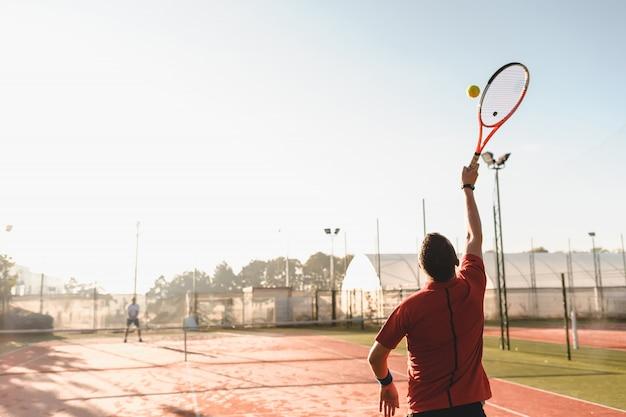 Jeune homme joue au tennis sur une fraîche matinée ensoleillée