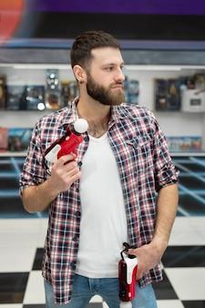 Un jeune homme joue sur une playstation, un joueur émotionnel tire le jeu avec un contrôleur de pistolet et sourit.