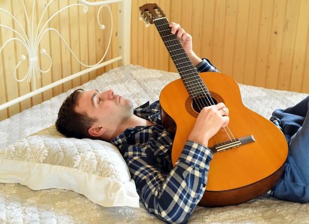 Jeune homme, jouer guitare, et, poser, lit