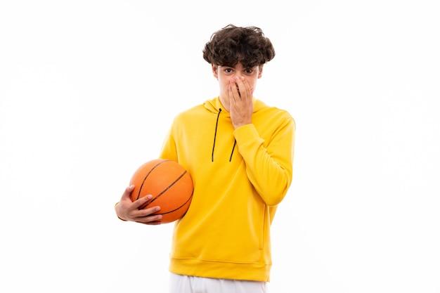 Jeune homme de joueur de basket sur un mur blanc isolé avec une expression faciale surprise