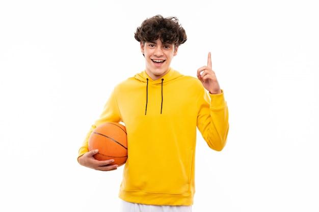 Jeune homme de joueur de basket sur un mur blanc isolé pointant vers le haut une excellente idée
