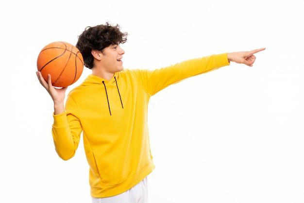 Jeune homme de joueur de basket sur un mur blanc isolé