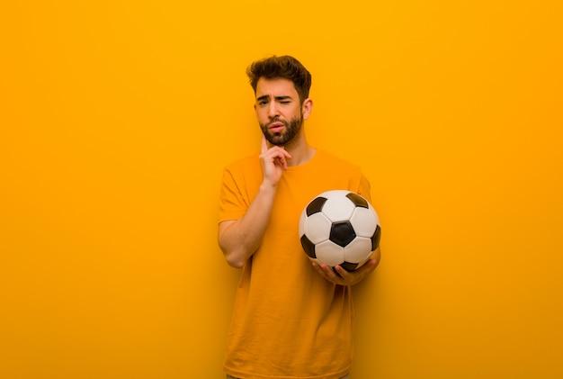 Jeune homme joueur de football doutant et confus