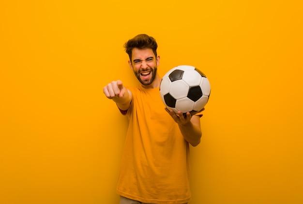 Jeune homme joueur de football gai et souriant