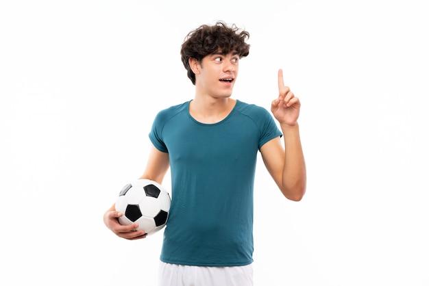 Jeune homme joueur de football sur mur blanc isolé visant à réaliser la solution tout en levant un doigt