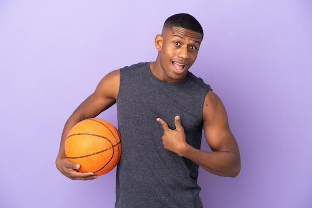 Jeune homme de joueur latin de basket-ball isolé sur un mur violet avec une expression faciale surprise