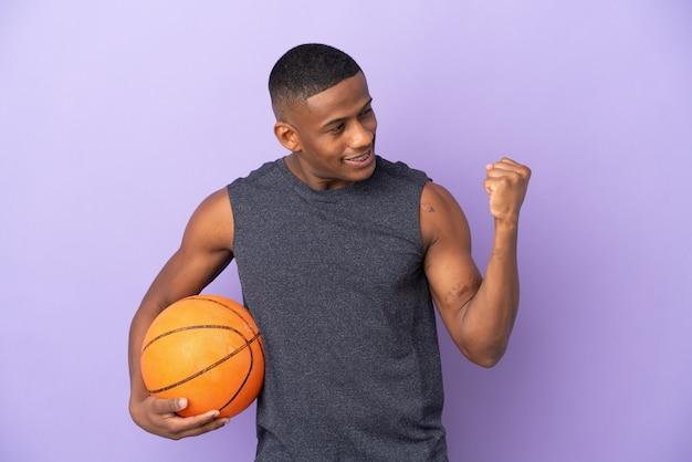 Jeune homme de joueur latin de basket-ball isolé sur violet célébrant une victoire