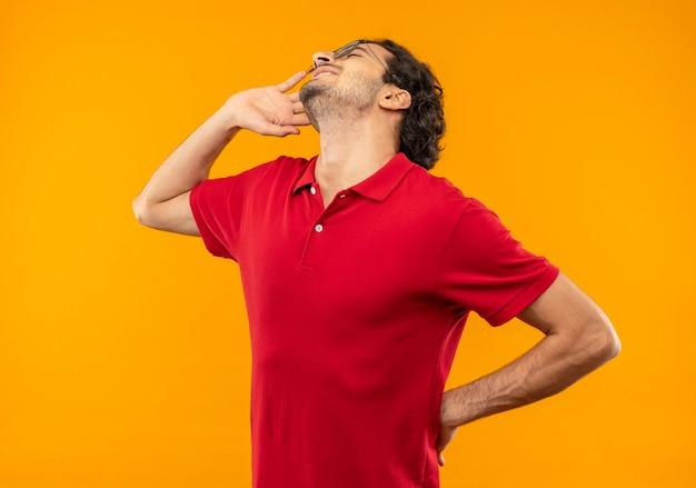 Jeune homme joyeux en chemise rouge avec des lunettes optiques tient le visage et met la main sur la taille avec les yeux fermés isolé sur le mur orange