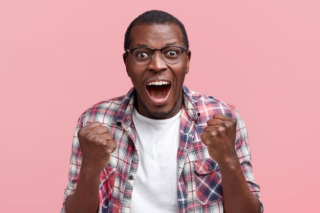 Un jeune homme joyeux et heureux serre les poings, porte une chemise à carreaux, s'exclame triomphant