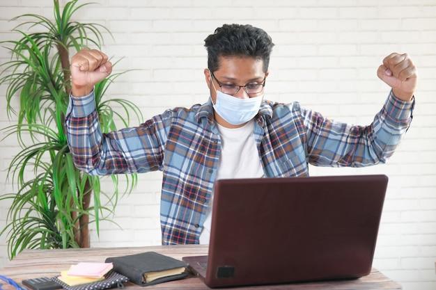 Jeune homme joyeux en masque facial travaillant sur ordinateur portable