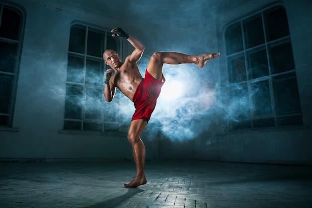 Le jeune homme kickboxing dans la fumée bleue