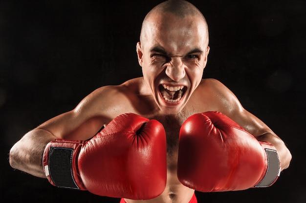 Le jeune homme kickboxing sur fond noir avec visage hurlant
