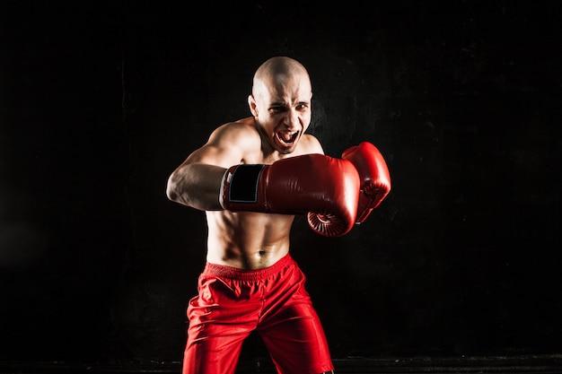 Le jeune homme kickboxing sur fond noir