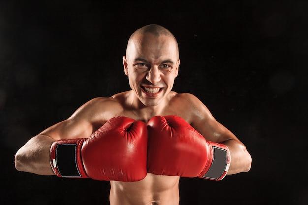 Le jeune homme kickboxing sur noir avec visage hurlant