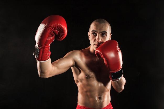 Jeune homme kickboxing sur noir