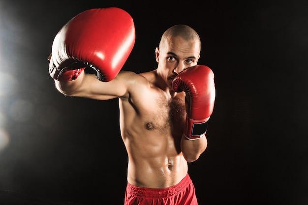 Le jeune homme kickboxing sur noir