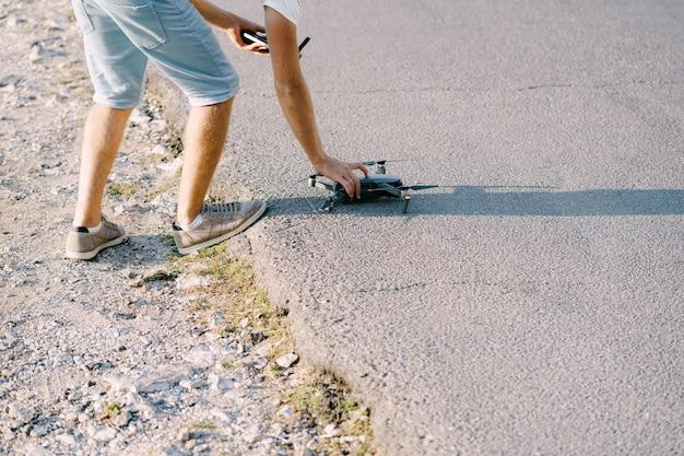 Un jeune homme lance un drone préparant le quadricoptère au décollage