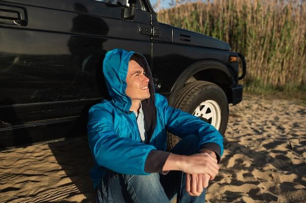 Jeune homme latin assis sur le sable appuyé contre un véhicule tout-terrain regardant vers l'avant en souriant tout en parlant avec quelqu'un. concept de voyage sur la route
