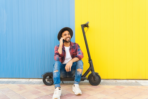 Jeune homme latin ayant un appel téléphonique tout en étant assis sur un scooter électrique.