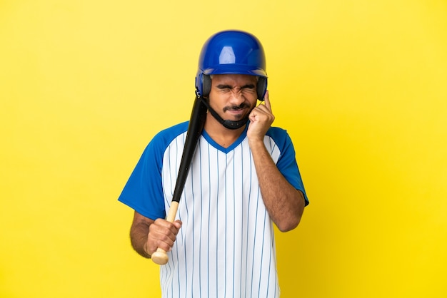 Jeune homme latin colombien jouant au baseball isolé sur fond jaune frustré et couvrant les oreilles