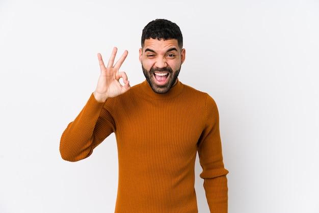 Jeune homme latin contre un mur blanc isolé clignote un œil et tient un geste correct avec la main.