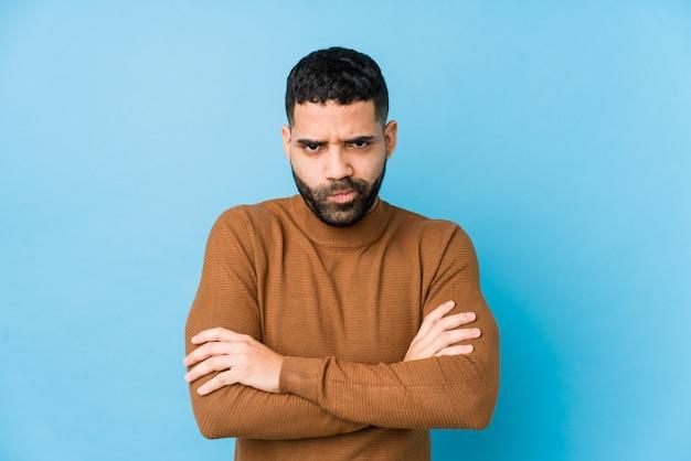 Jeune homme latin contre un mur bleu isolé face fronçant les sourcils de mécontentement, garde les bras croisés.