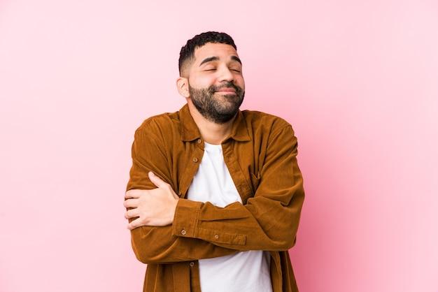 Jeune homme latin contre un mur rose étreintes isolées, souriant insouciant et heureux.