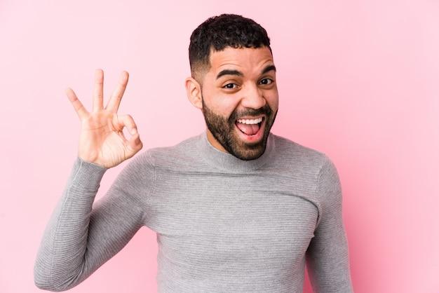 Un jeune homme latin contre un mur rose fait un clin d'œil et tient un geste correct avec la main.