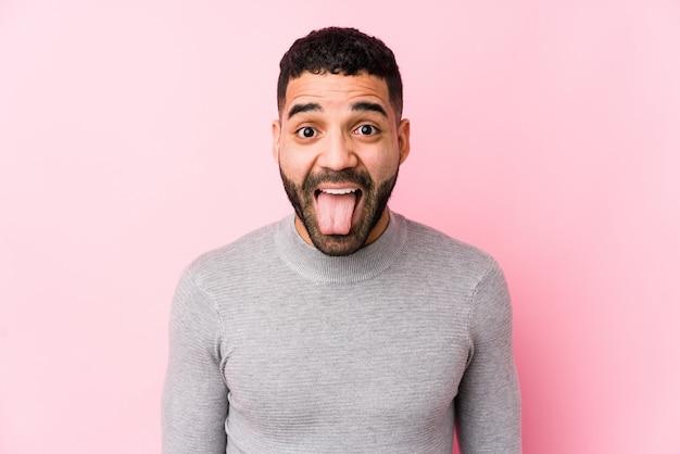 Jeune homme latin contre un mur rose isolé drôle et sympathique qui sort la langue.