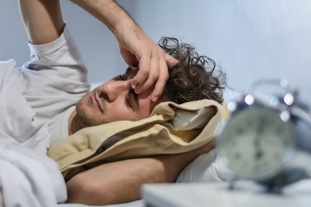 Jeune homme latin dort avec réveil.