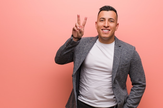 Jeune homme latin élégant amusant et heureux faisant un geste de victoire