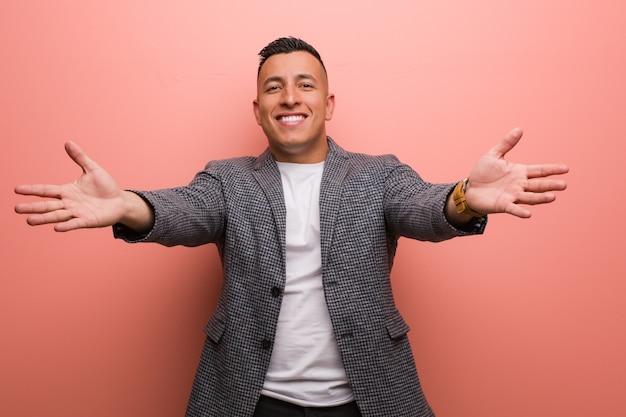 Jeune homme latin élégant très heureux donnant un câlin à l'avant