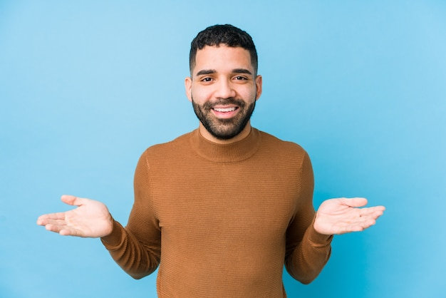 Jeune homme latin sur fond bleu isolé montrant une expression de bienvenue.