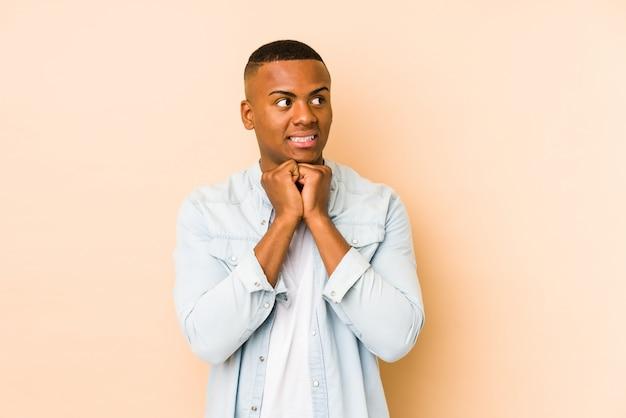 Jeune homme latin isolé sur beige garde les mains sous le menton, regarde joyeusement de côté.