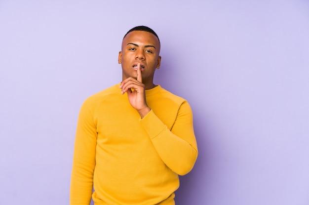 Jeune homme latin isolé sur mur violet gardant un secret ou demandant le silence.
