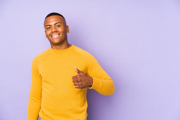 Jeune homme latin isolé sur mur violet souriant et levant le pouce vers le haut