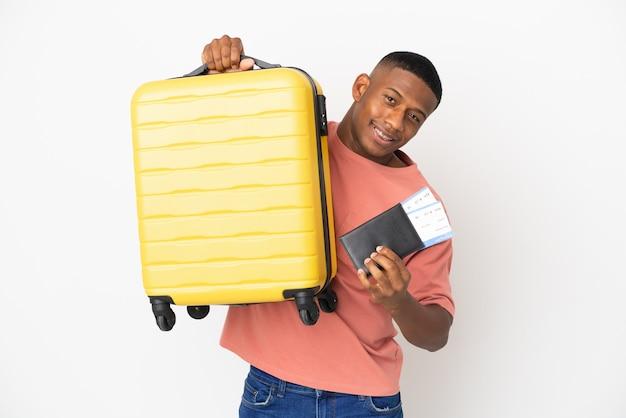 Jeune homme latin isolé en vacances avec valise et passeport