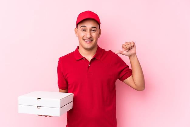 Jeune homme latin de livraison de pizza isolé se sent fier et confiant, exemple à suivre.