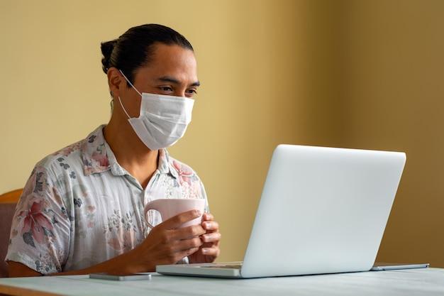 Jeune homme latin avec masque médical travaille détendu à la maison. copiez l'espace. concept de coronavirus.