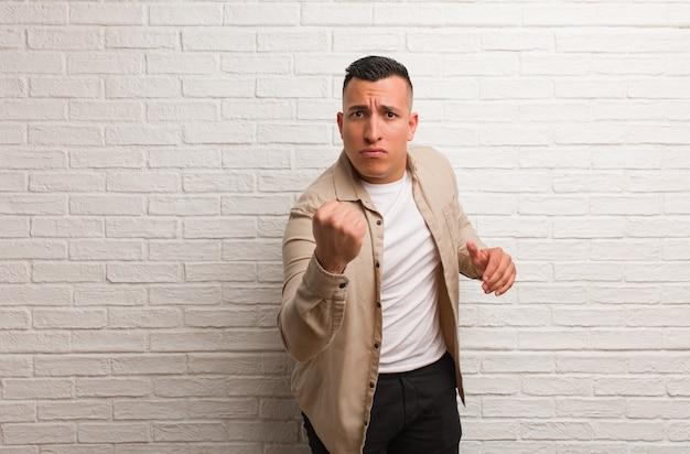 Jeune homme latin montrant le poing devant, expression fâchée