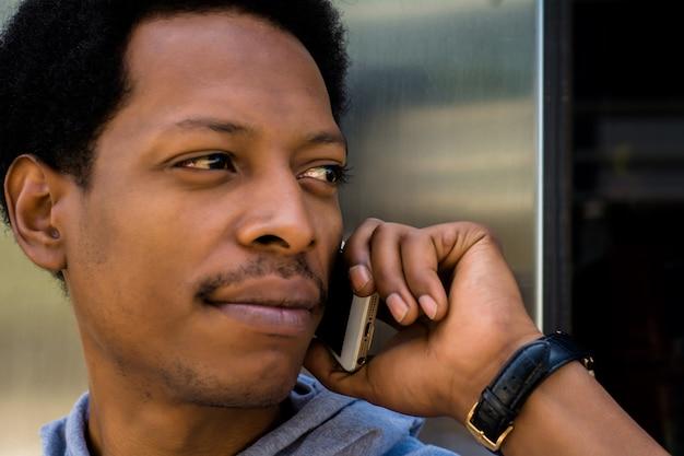 Jeune homme latin parle sur son téléphone portable à l'extérieur.