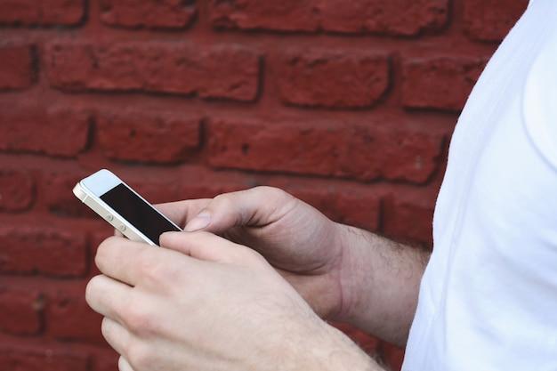 Jeune homme latin tapant sur son téléphone
