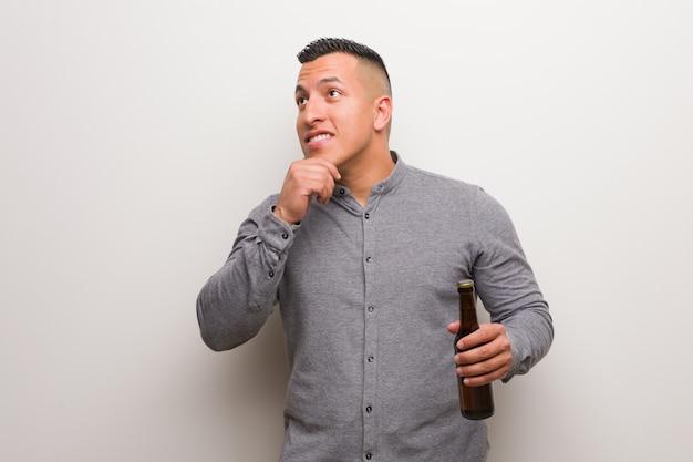 Jeune homme latin tenant une bière doutant et confus