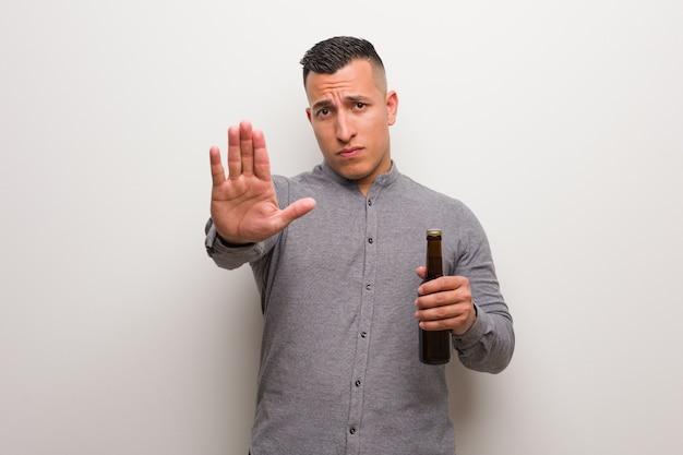 Jeune homme latin tenant une bière en mettant la main devant