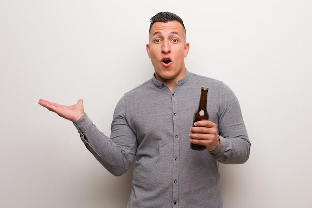 Jeune homme latin tenant une bière tenant quelque chose sur la main de la paume