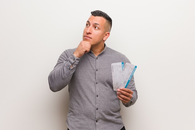 Jeune homme latin tenant un billet d'avion détendu en pensant à quelque chose en regardant un espace copie